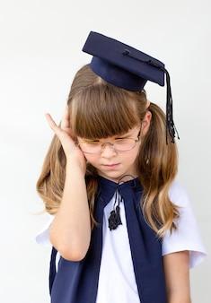 Triste petite étudiante diplômée déçue en robe de graduation noire avec chapeau - isolée sur blanc. expression faciale d'émotion humaine négative. enfant de retour à l'école, concept éducatif.