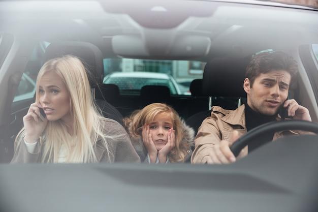Triste petite fille assise dans la voiture pendant que ses parents parlent