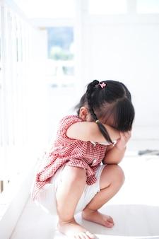 Triste petite fille assise sur le sol dans une pièce vide