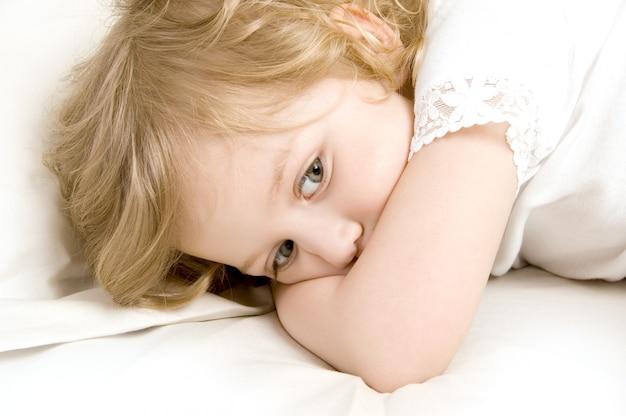 Triste petite fille dans le lit