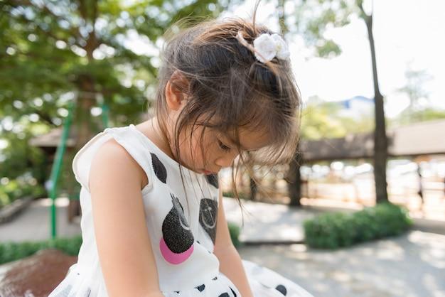 Triste petite fille dans le parc
