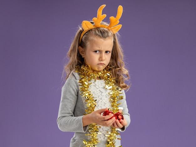 Triste petite fille portant un cerceau de cheveux de noël avec guirlande sur le cou tenant des boules de noël isolé sur fond bleu