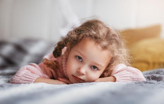 Triste petite fille se trouve sur le canapé