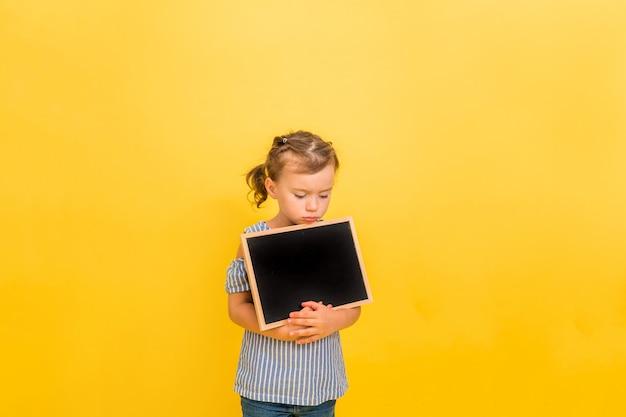 Une triste petite fille tient une ardoise sur jaune
