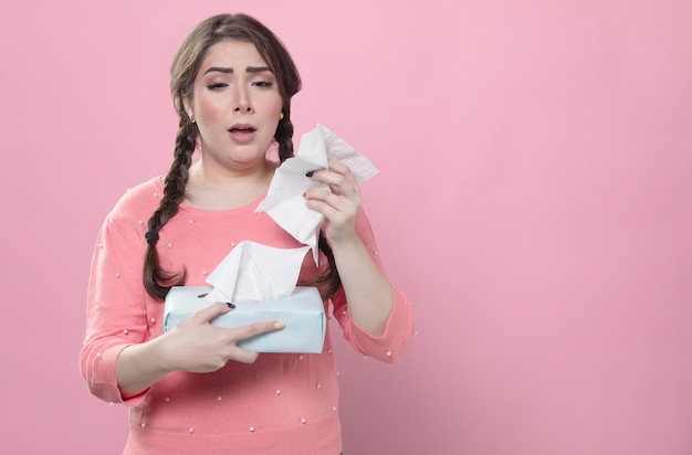 Triste sur le point d'éternuer tout en tenant des serviettes