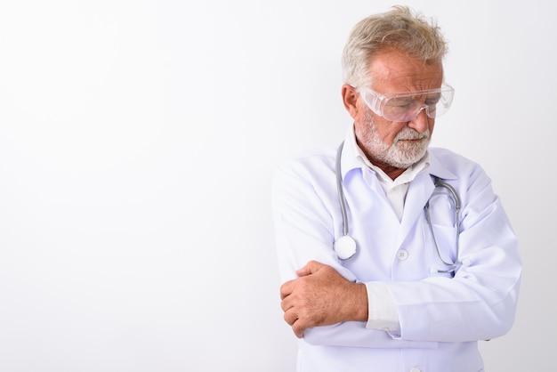 Triste senior homme barbu médecin pensant tout en portant des lunettes de protection avec les bras croisés sur blanc