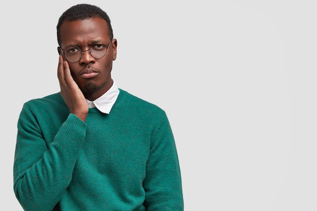 Triste, solitaire, insatisfait, jeune homme noir garde la main sur la joue, se sent mécontent
