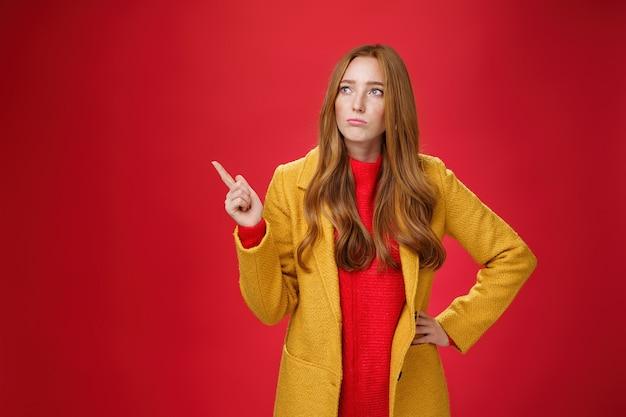 Triste et sombre fille au gingembre mignonne dans les années 20 portant un manteau jaune à la mode tenant la main sur la taille, faisant la moue, regardant et pointant vers le coin supérieur gauche avec regret et chagrin sur fond rouge.