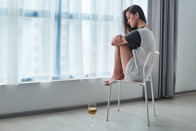 Triste stressé malheureux déprimé mélancolique femme pensive avec verre de vin assis seul à la maison près de la fenêtre lors de problèmes de vie et de dépression
