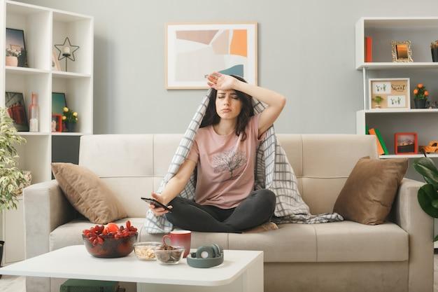 Triste, les yeux fermés, mettant la main sur le front, jeune fille enveloppée dans un plaid tenant un téléphone assis sur un canapé derrière une table basse dans le salon