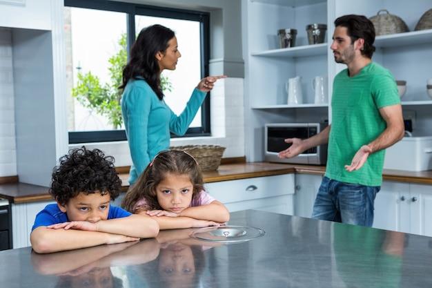 Tristes enfants écoutant les arguments des parents