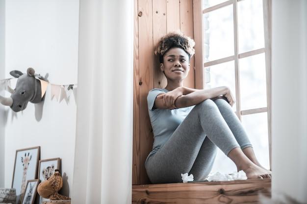 Tristesse, émotion. déprimé jeune femme à la peau sombre pieds nus dans des vêtements à la maison assis sur le rebord de la fenêtre à la chambre
