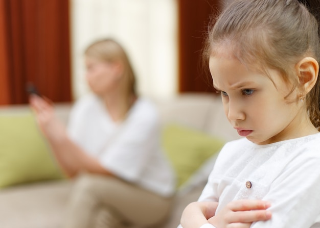 Tristesse jeune fille. portrait de fille s'ennuie avec sa mère à l'aide de téléphone portable sur le lit. relations de famille.