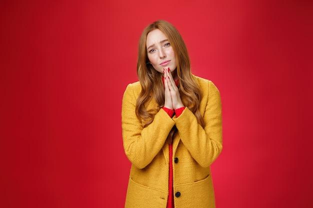 Tristesse et triste petite amie rousse séduisante en manteau jaune implorant la miséricorde, pleine d'espoir et contrariée par les mains en train de prier et de froncer les sourcils, s'excusant de demander pardon sur fond rouge.