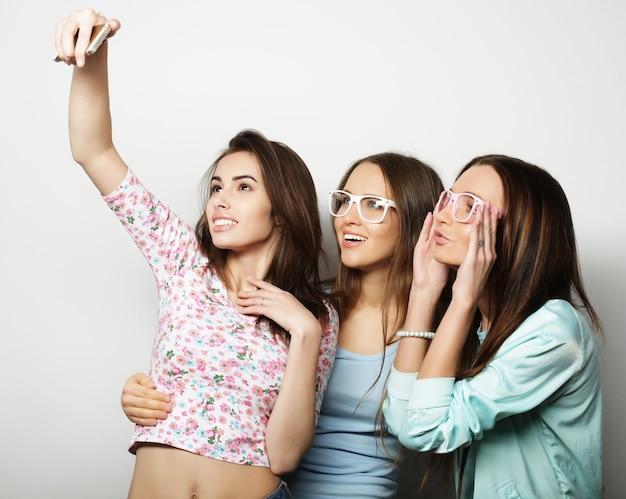 Trois adolescentes heureuses hipster avec smartphone prenant selfie
