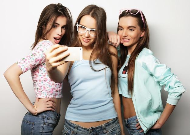 Trois adolescentes hipster heureux avec smartphone prenant selfie