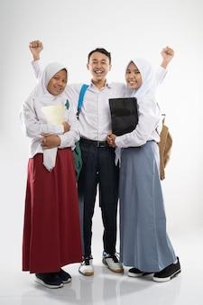 Trois adolescents souriants portant des uniformes scolaires avec un sac à dos, un livre et un ordinateur portable