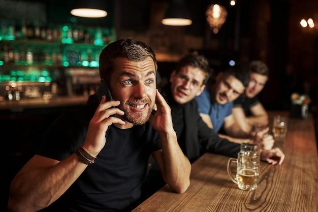 Trois amateurs de sport dans un bar en regardant le football