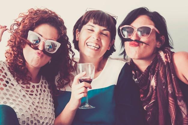 Trois amies caucasiennes restent ensemble dans l'amitié et la folie en utilisant des cheveux comme la moustache et le concept de relation de bonheur