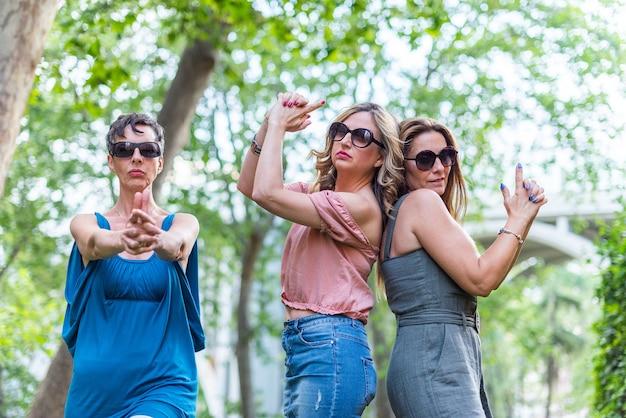Trois amies matures faisant un geste d'arme à feu avec leurs mains et posant. amies d'âge moyen s'amusant.