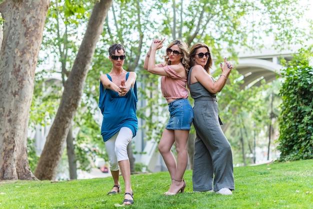 Trois amies matures faisant un geste d'arme à feu avec leurs mains et posant dans le parc. amies d'âge moyen s'amusant.