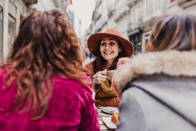 Trois amies prenant un café sur une terrasse à porto, au portugal. avoir une conversation amusante