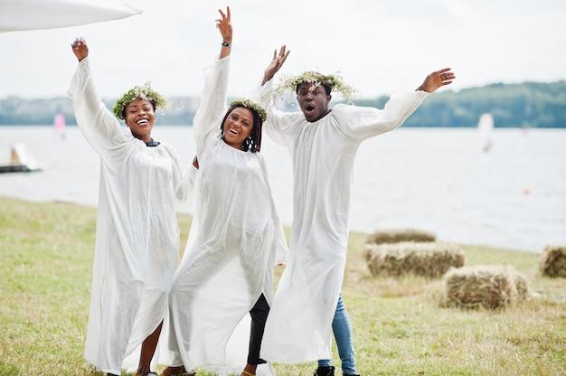 Trois amis afro-américains sur des capes blanches et une couronne s'amusant ensemble.