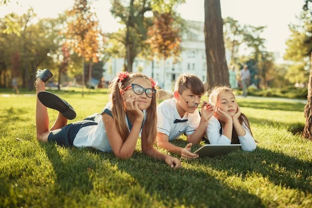 Trois amis d'âge scolaire souriants sont allongés sur l'herbe. dans les mains des enfants, une tablette
