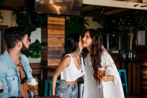 Trois amis disent bonjour au bar