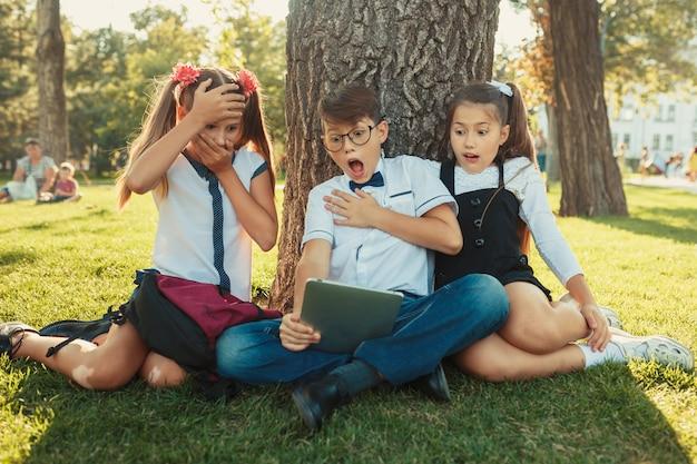 Trois amis d'école adolescentes souriantes assis dans le parc sur l'herbe et jouant ensemble nouveau jeu de tablette. différentes émotions sur leurs visages