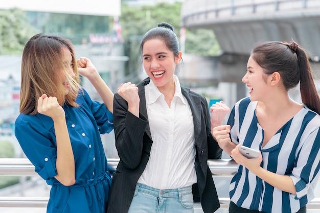 Trois amis de l'équipe de travail célèbrent en plein air