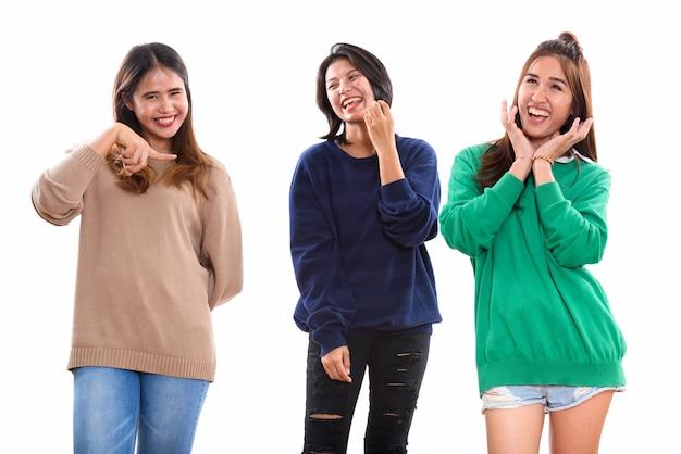 Trois amis heureux jeune femme asiatique souriant et faisant des grimaces avec un ami doigt pointé