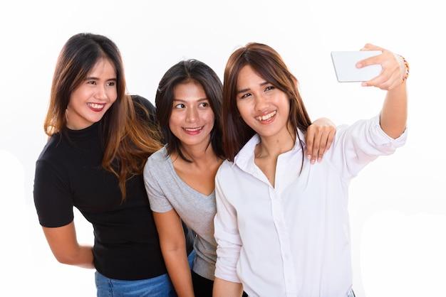 Trois amis heureux jeune femme asiatique souriant tout en prenant une photo de selfie avec un téléphone mobile