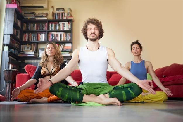 Trois amis méditant dans leur appartement