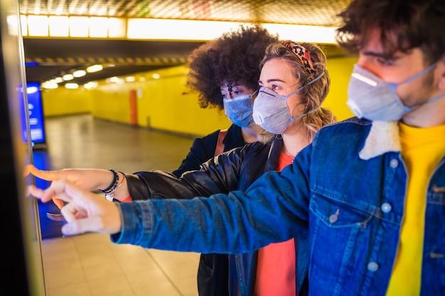 Trois amis multiethniques portant un masque médical protégeant de la pollution et des virus à l'aide d'un écran tactile