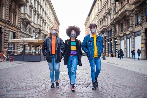 Trois amis multiethniques portant un masque médical protégeant de la pollution et des virus