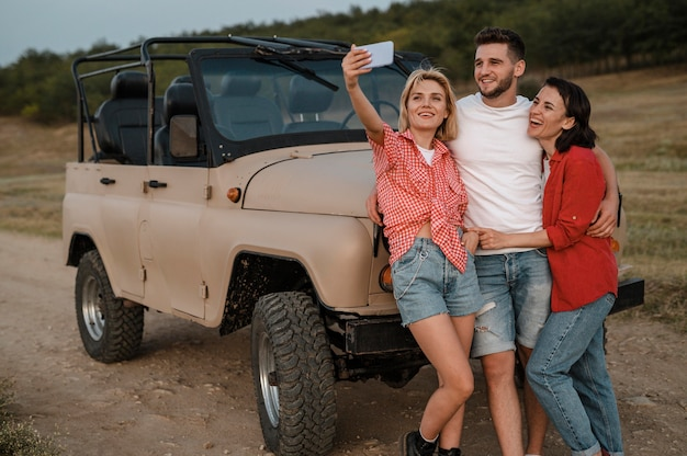 Trois amis prenant selfie en voyageant en voiture