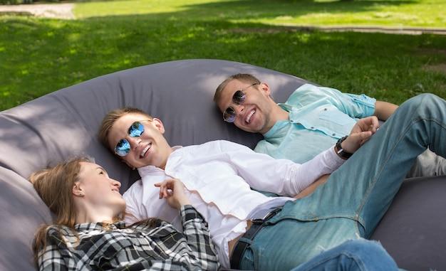 Trois amis qui rient heureux se détendre en plein air dans le parc sur un grand coussin d'oreiller.