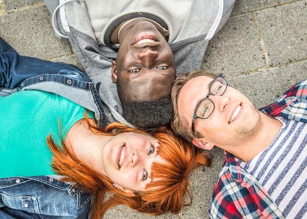 Trois amis de race mixte gisant sur le sol
