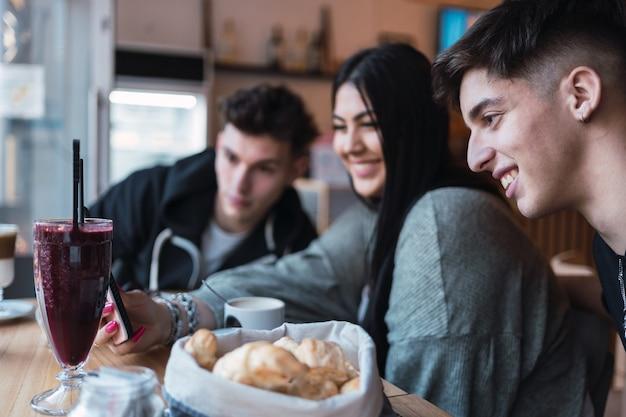 Trois amis regardent joyeusement les médias sociaux avec un smartphone dans un café.