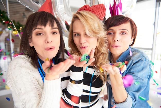 Trois amis soufflant des confettis