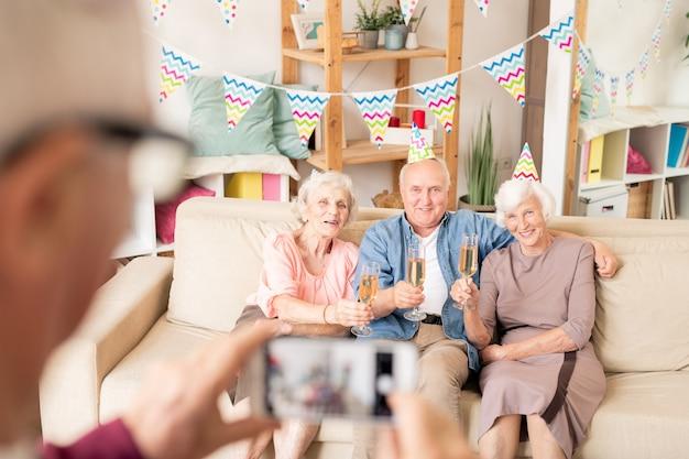 Trois amis supérieurs avec des flûtes de champagne assis sur un canapé tout en portant un toast pour anniversaire