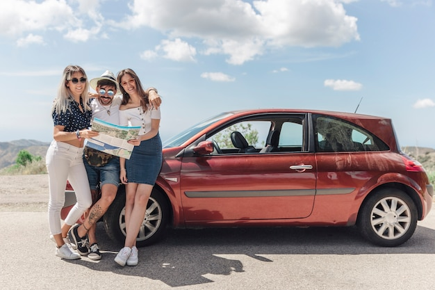Trois amis tenant la carte debout près de la voiture moderne sur route