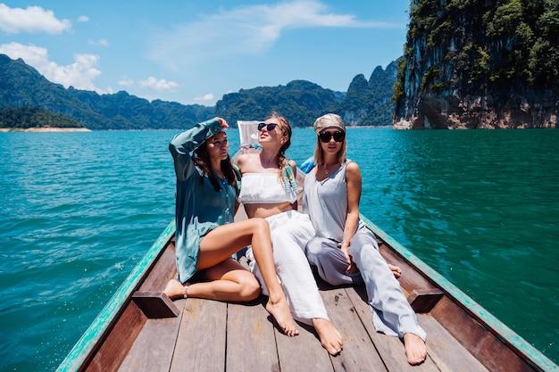 Trois amis touristes voyagent autour du parc national de khao sok, en vacances en thaïlande. voile sur un bateau asiatique sur le lac en journée ensoleillée, avec une vue imprenable.