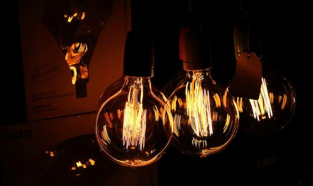 Trois ampoules faiblement éclairées dans une zone sombre