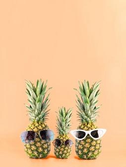 Trois ananas avec des lunettes sous la forme d'une famille de trois personnes en vacances. concept de voyage d'été dans les pays tropicaux