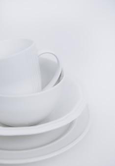 Trois assiettes blanches et une tasse sur un fond blanc