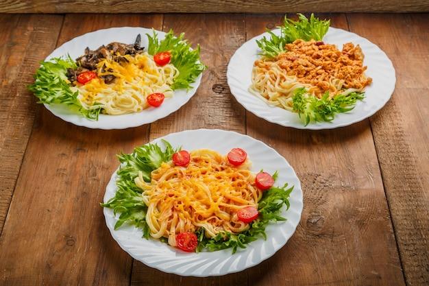 Trois assiettes avec différentes pâtes sur une table en bois. photo horizontale