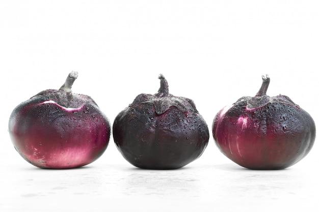 Trois aubergines rondes fraîches sur un blanc