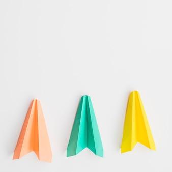 Trois avions en papier colorés dans la rangée